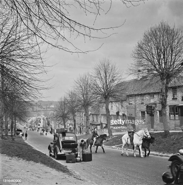 Mobile Film Unit operator from the Ministry of Information unpacks equipment from the boot of his car on The Hill in the Cotswold town of Burford,...