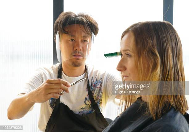 Mobile hairdresser Masaya Shibasaki with a customer as his business resumed operating on the coast road on July 5 2020 in Falmouth United Kingdom...