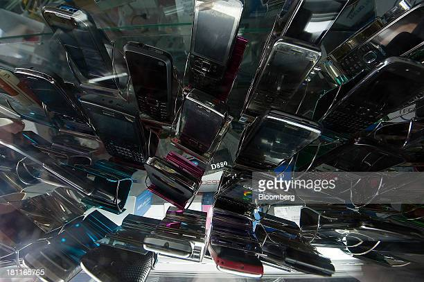 Mobile handsets sit on a display on the counter of a phone retailer in Kigali Rwanda on Wednesday Sept 18 2013 Coffeeproducing Rwanda's economy has...