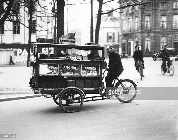Mobile household cleaning product shop powered by a bicycle travelling along a street in The Hague, Holland.