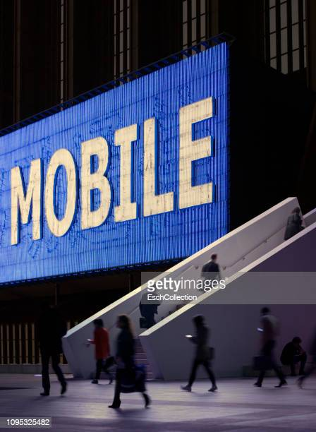 Mobile neon sign at modern business district with commuters