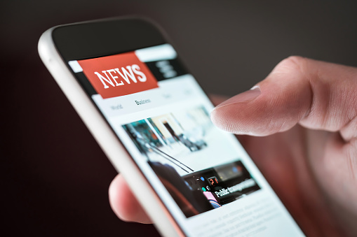 Mobile news application in smartphone. Man reading online news on website with cellphone. Person browsing latest articles on the internet. 1065782390