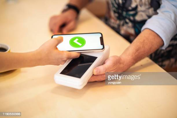 mobile payment in a coffee shop - money transfer stock pictures, royalty-free photos & images