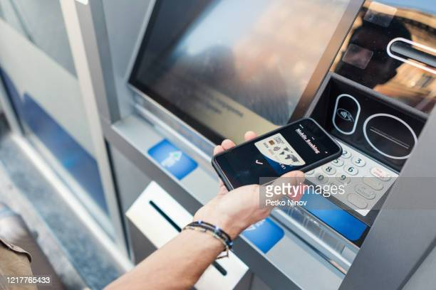 mobile payments at the atm - nfc stock pictures, royalty-free photos & images