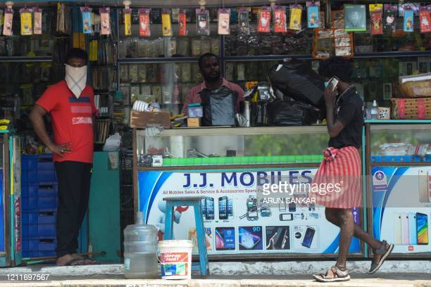 A mobile phone accessories shop owner waits for customers after the government eased a nationwide lockdown imposed as a preventive measure against...