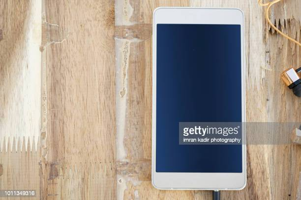 mobile phone an ear phone  on wooden table. - iphone mockup stock pictures, royalty-free photos & images