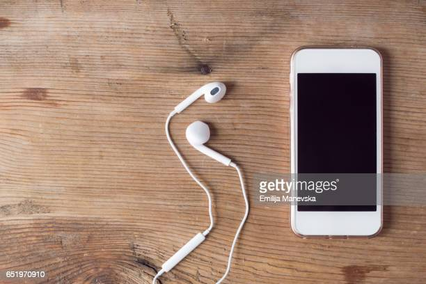 Mobile Phone and earings on wooden table