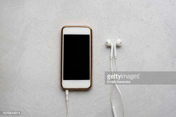mobile phone and headphones on white background - podcast stock-fotos und bilder