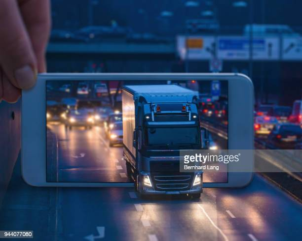 Mobile Phone displaying a truck driving through the phone