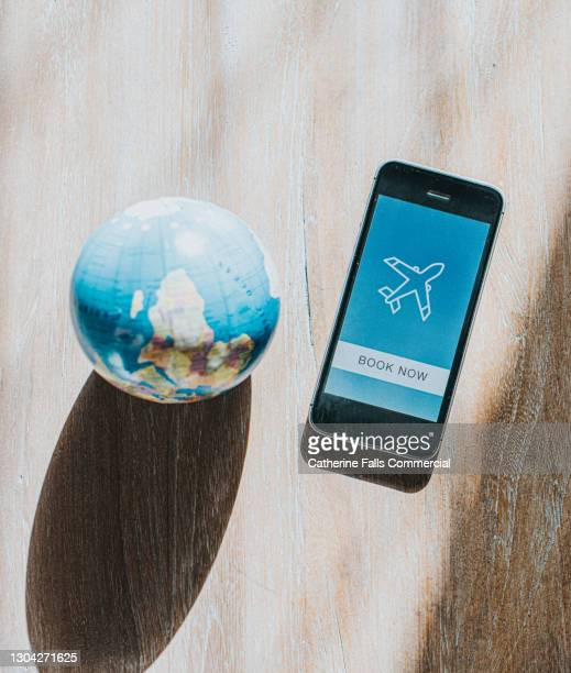 mobile phone displaying an air travel booking app beside a globe - passenger craft stock pictures, royalty-free photos & images