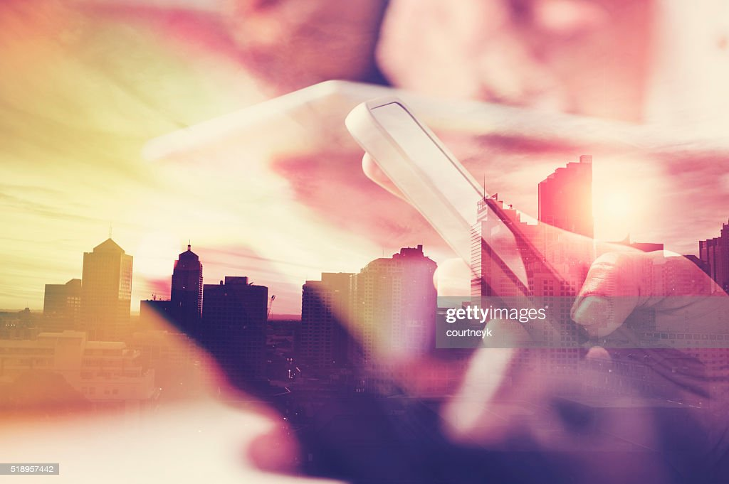 Mobile phone in hand with city skyline. : Stock Photo