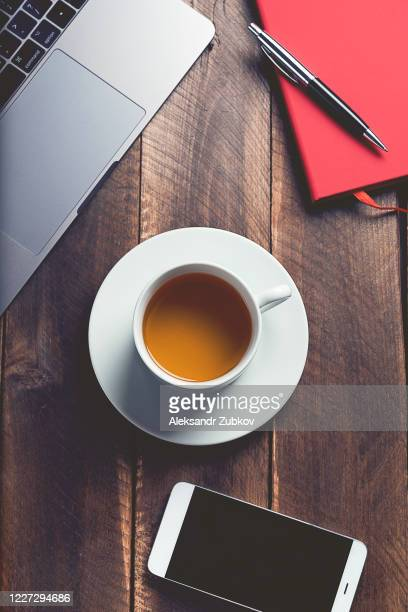 mobile phone, laptop, pen and notepad for notes, a cup of tea, at the workplace. - high section stock pictures, royalty-free photos & images