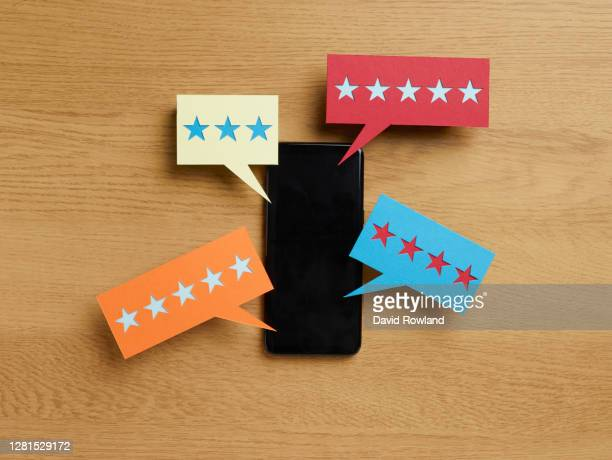 mobile phone on a table top with coloured symbols with star ratings around it - feedback stockfoto's en -beelden