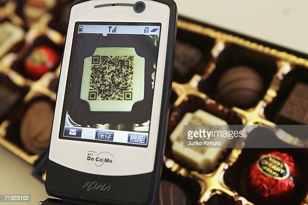 A mobile phone reads a piece of chocolate decorated with a URL written in twodimensional code on June 29 2006 in Tokyo Japan The chocolate is...