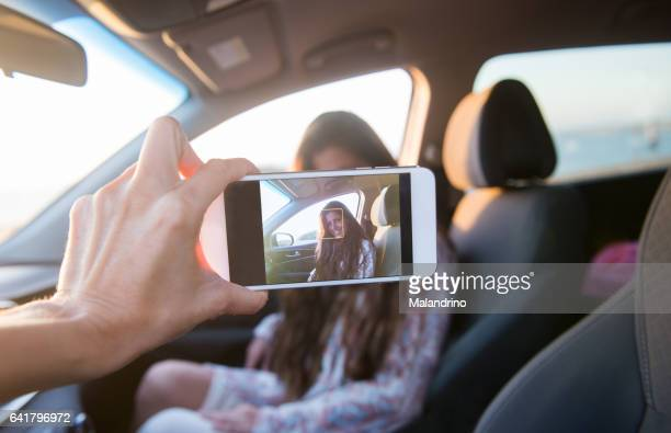 A mobile phone showing the picture of a woman that is seated on a car