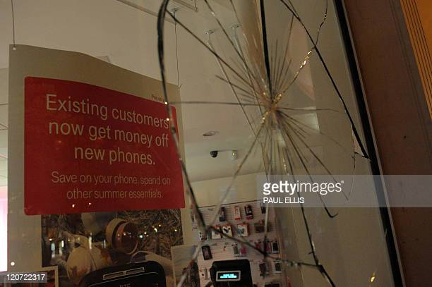 A mobile phone store window is seen smashed in the city centre of Birmingham central England on August 8 2011 during a night of unrest Violence...