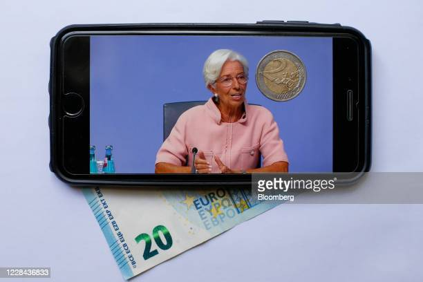A mobile phone surrounded by Euro currency displays Christine Lagarde president of the European Central Bank during a live stream video of the...
