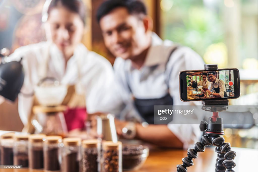 Mobile phone taking Video to two Asian Barista presenting a cup of coffee, dripping coffee show to audience in coffee shop,making espresso and americano, Small business owner and startup concept : Stock Photo