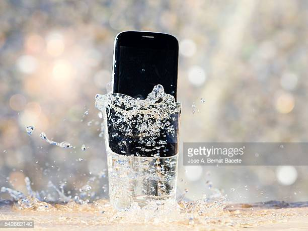 Mobile phone that has fallen down inside a glass for accident.