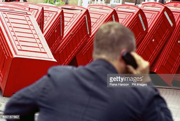 A mobile phone user makes a call in front of a row of disused telephone boxes that have been turned into an urban sculpture in KingstonuponThames SW...