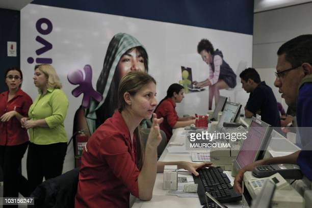 A mobile phone vendor explains instructions to a client while buying a new mobile at a Vivo shop in Sao Paulo Brazil on July 29 2010 Shares in Vivo...