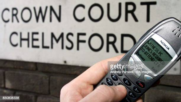 A mobile phone with a court text message Courts minister Michael Wills at Chelmsford Crown Court launch a 24 million pilot project which will send...