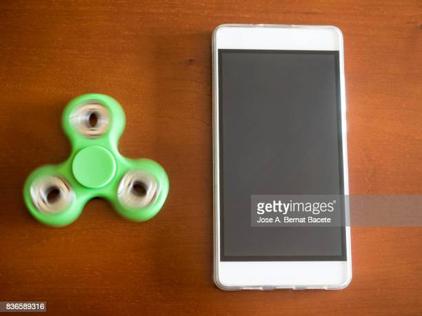 Mobile phone with a toy fidget spinner on a table. Spain