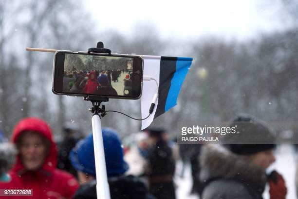A mobile phone with an Estonian flag is held during a festive ceremony in front of the Estonian Parliament to celebrate 100 years since Estonia...