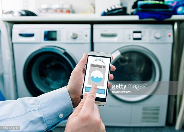 mobile phone with app used to control washing machines - smart stock pictures, royalty-free photos & images