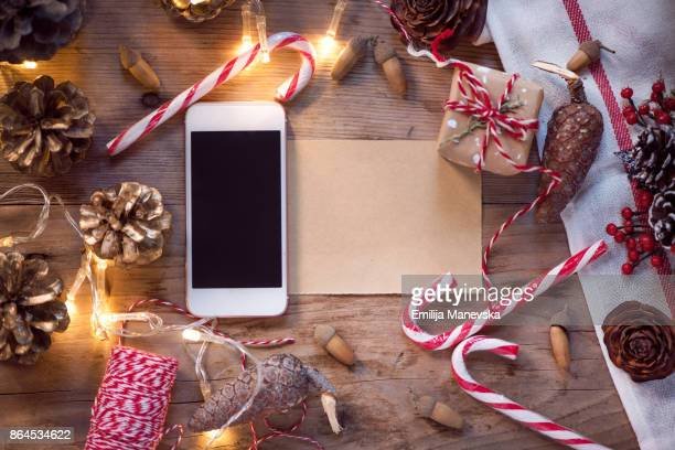 Mobile Phone With Blank Screen And Christmas Ornaments On Wooden Retro Styled Background