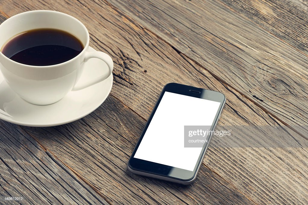 Mobile phone with coffee on a wooden table. : Stock Photo