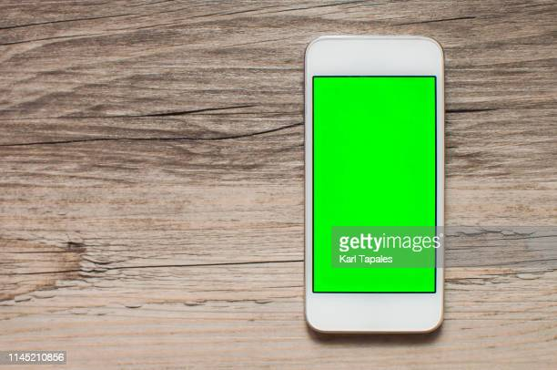 a mobile phone with green screen on a wooden table - chroma key imagens e fotografias de stock