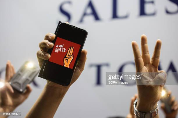Mobile phone with the three finger salute, demonstrating against the military coup. Myanmar demonstrators gathered in front of the Myanmar Embassy in...