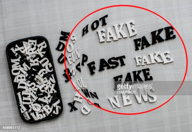 Mobile phone-cover with wooden letters and the word 'Fake'.