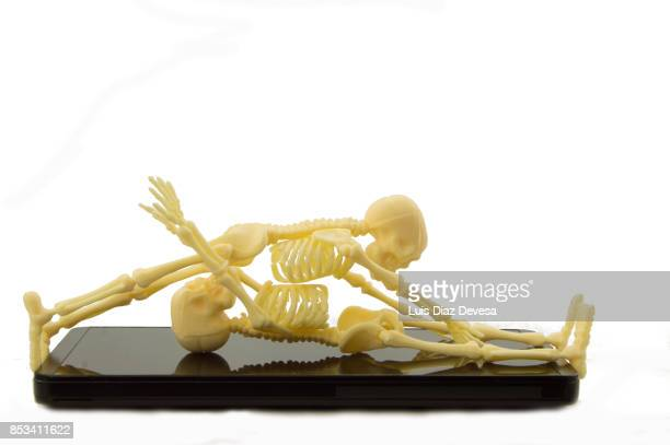 mobile phones interfere in a couple's relationship - human skeleton stock photos and pictures