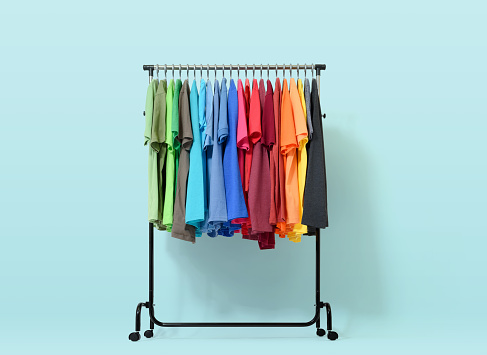 Mobile rack with color clothes on light blue background 645316048