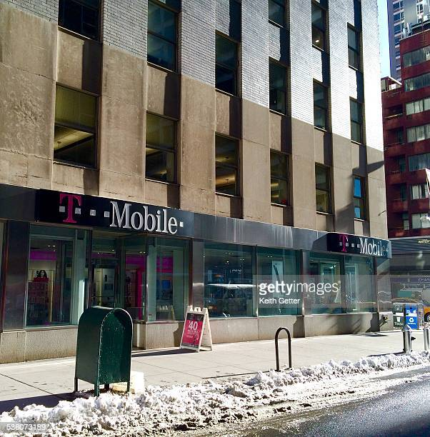 T Mobile retail storefront at a ground level urban street corner location in the Financial District in Manhattan NYC on a bright winter afternoon