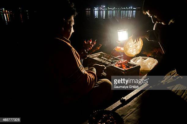 CONTENT] A mobile shop in boat is selling eatables like barbecued kebabs on the Dal lake at night