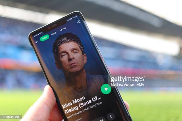 Mobile telephone with the Spotify app on listening to Blue Moon Rising by Manchester City fan Noel Gallagher and his band the High Flying Birds at...