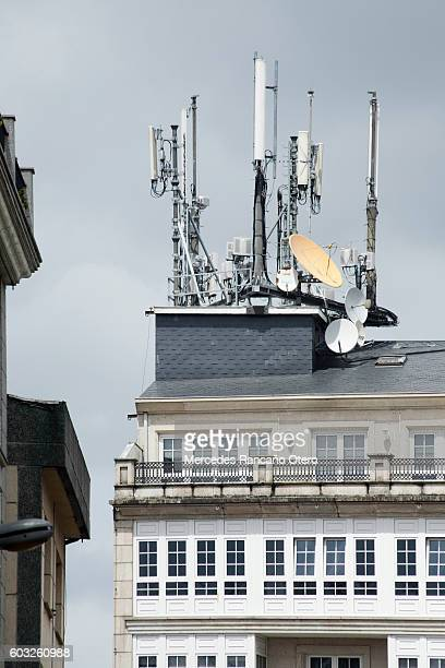 Mobile telephony and television relay antennas on residential building roof.