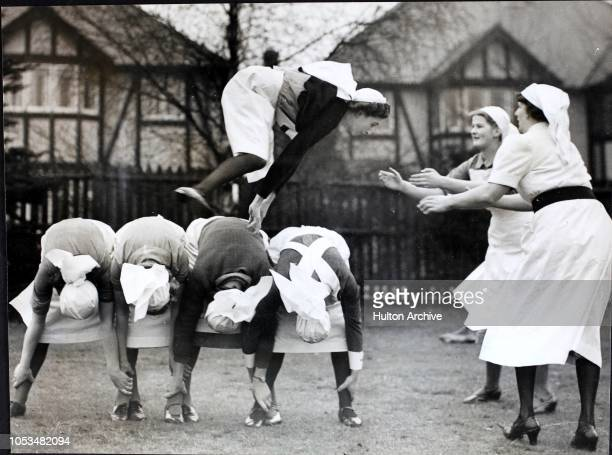 Mobile Unit and Red Cross nurses at an ARP centre in Southgate keep warm and keep fit with a game of leapfrog England World War II This Red Cross...