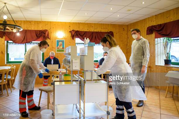 Mobile vaccination team is waiting for another resident to be vaccinated with the Pfizer-BioNTech vaccine against COVID-19 in an old clubhouse during...
