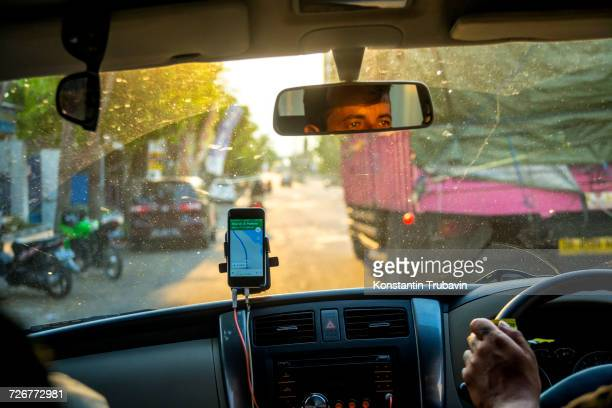 A Mobilephone With GPS Apps In Car To Navigate Around Jakarta