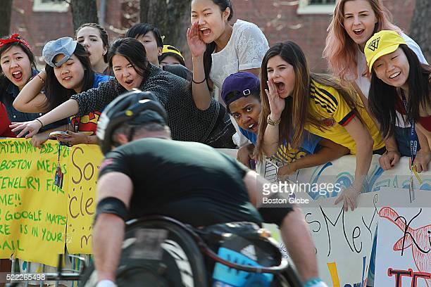 A mobility impaired competitors is cheered on by the Wellesley College students in the Scream Tunnel at Wellesley College along the route of the...