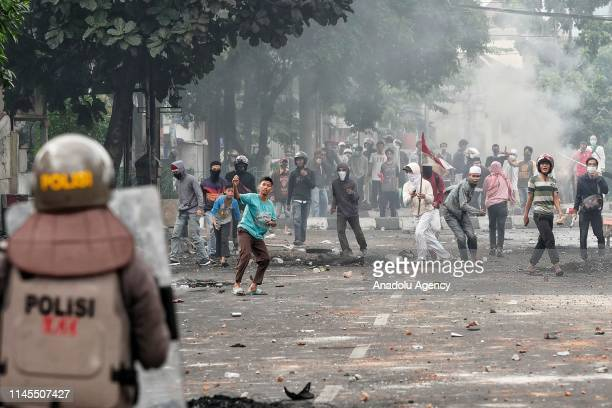 Mobs throw stones toward the police in the Tanah Abang Market area Jakarta Indonesia on May 22 2019 This clash triggered aftermath of a mass...