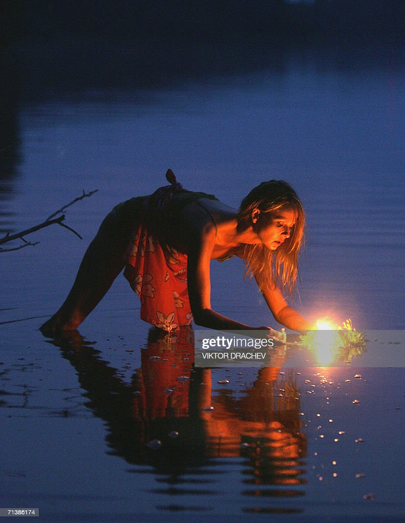 a girl lays a wreath with a candle on the water of the lake of