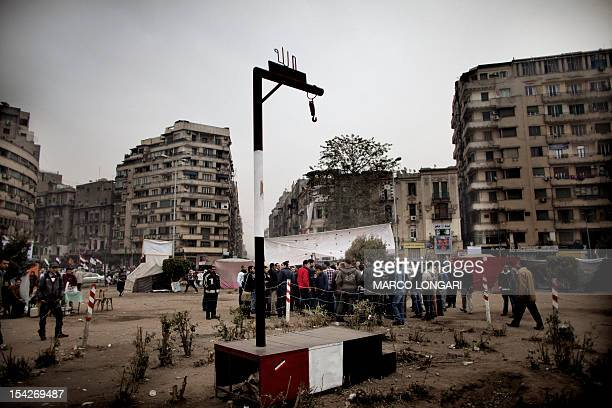 Mock gallows stand in the middle of Tahrir square in Cairo as a group of Egyptians gather nearby for politicallyorientated discussions on February 14...