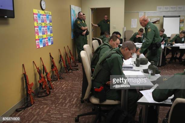 Mock M4 rifles line the wall as new Border Patrol agents attend a Spanish language class at the US Border Patrol Academy on August 2 2017 in Artesia...