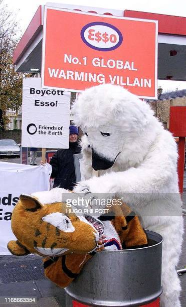 A mock polar bear cans the Esso tiger 01 December 2001 during a Greenpeacesponsored demonstration at an Esso gasoline station in West London...