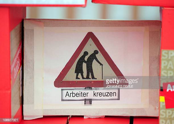 A mock street sign featuring an elderly couple crossing and reading 'Workers cross' is displayed during demonstration against the governement's...